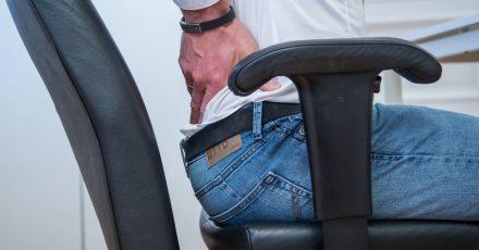 Problem und Lösung in einem Bild: Eine gekräftigte Muskulatur beugt Schmerzen vor - als Trainingshilfe im Büro können dabei auch die Armlehnen des Stuhls herhalten.