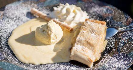 Der Klassiker unter den Strudeln ist der Apfelstrudel. Hier wird er mit Vanilleeis und Sahne und Puderzucker serviert.