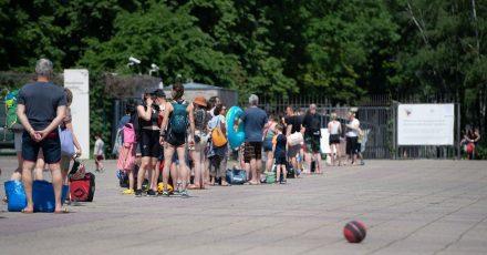 Menschen stehen bei warmem Wetter in einer Schlange vor dem Eingang zum Olympiabad in Berlin.