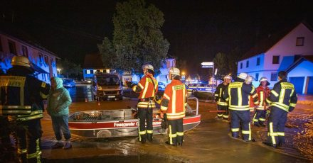 Feuerwehrleute im Kreis Biberach stehen neben einem Feuerwehrboot auf einer Straße in den Fluten eines heftigen Unwetters.