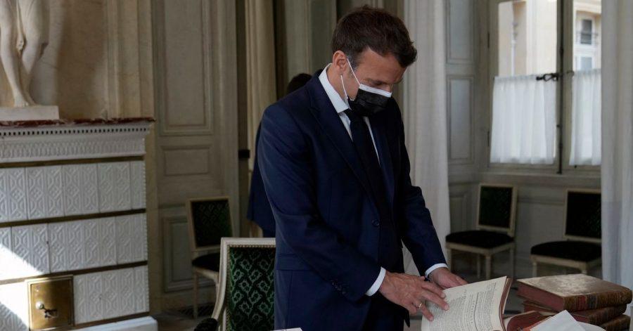 Präsident Emmanuel Macron blättert in alten Büchern.