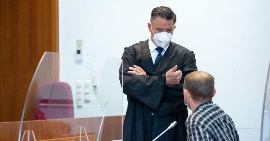 Einer der Angeklagten (r) unterhält sich vor Prozessbeginn mit seinem Verteidiger Dietmar Bonn.