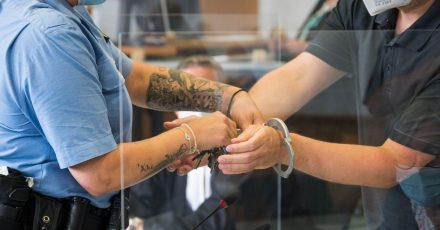 Eine Justizbeamtin (l) nimmt dem Angeklagten die Handschellen ab. Der 29-jährige Krankenpfleger muss sich wegen versuchten Mordes vor Gericht verantworten.