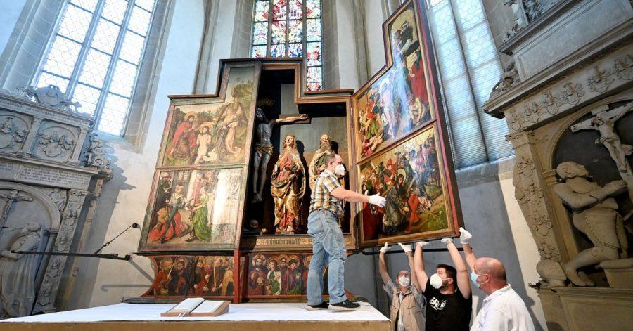 Um ein möglicherweise neu entdecktes Werk von Albrecht Dürer sichtbar zu machen, klappen Kirchenmitarbeiter der Johanneskirche ihren spätgotischen Flügelaltar zu.