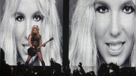 """Madonna bei einem Auftritt ihrer """"Sticky and Sweet""""-Tour im Jahr 2009 - mit Britney-Spears-Foto im Hintergrund.  (ili/spot)"""