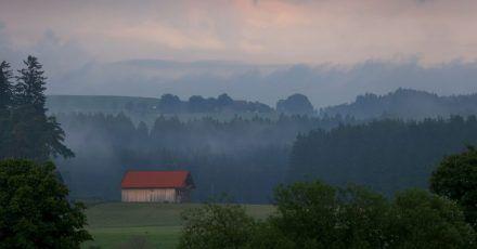 Eine Holzhütte steht im Abendlicht in der wolkenverhangenen Allgäuer Landschaft bei Marktoberdorf. (Archivbild)