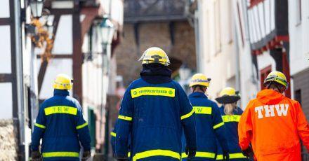 Mitglieder des Technischen Hilfswerks (THW) gehen bei Räumarbeiten nach der Unwetter-Katastrophe in Nordrhein-Westfalen durch einen zerstörten Ort.