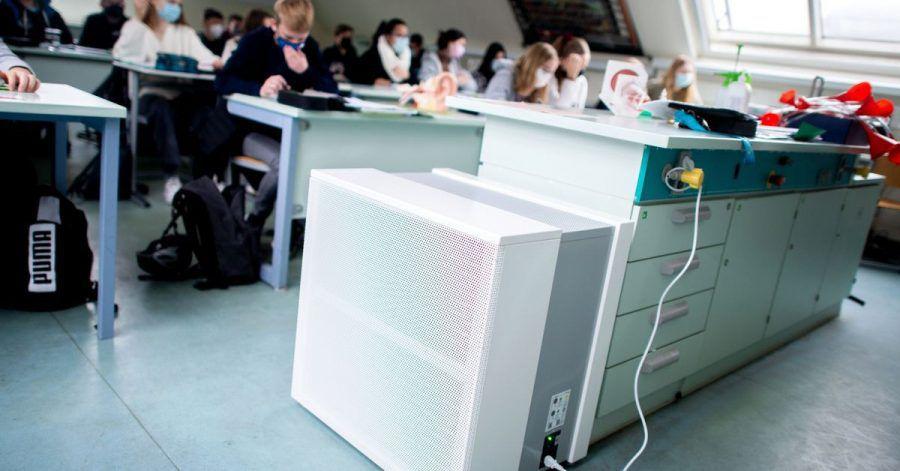 Ein Luftfiltergerät steht in einem Schulraum. Mobile Luftfiltergeräte sollen die Konzentration von Aerosolen in Klassenräumen senken.