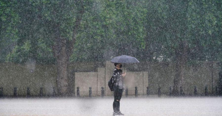 Eine Frau in London schützt sich mit einem Schirm vor dem starken Regen.