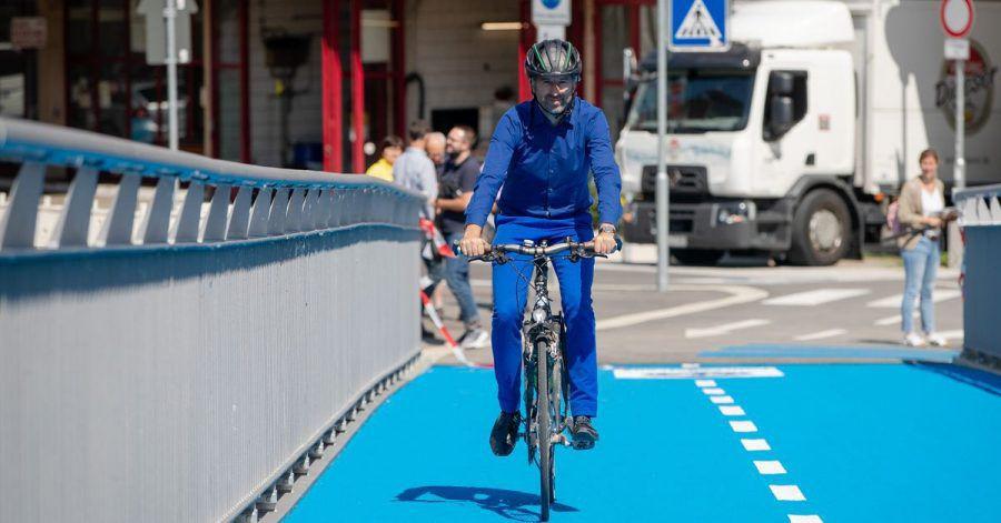 Oberbürgermeister Boris Palmer rollt über die erste beheizbare Radbrücke in Tübingen.