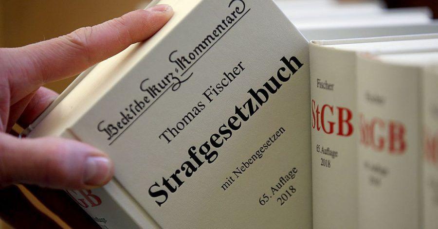 Illustration - Ein Jurist nimmt das Strafgesetzbuch aus dem Regal. In Bayern muss sich ein junger Polizist unter anderem wegen des Besitzes kinderpornografischer Schriften vor einem Gericht verantworten.