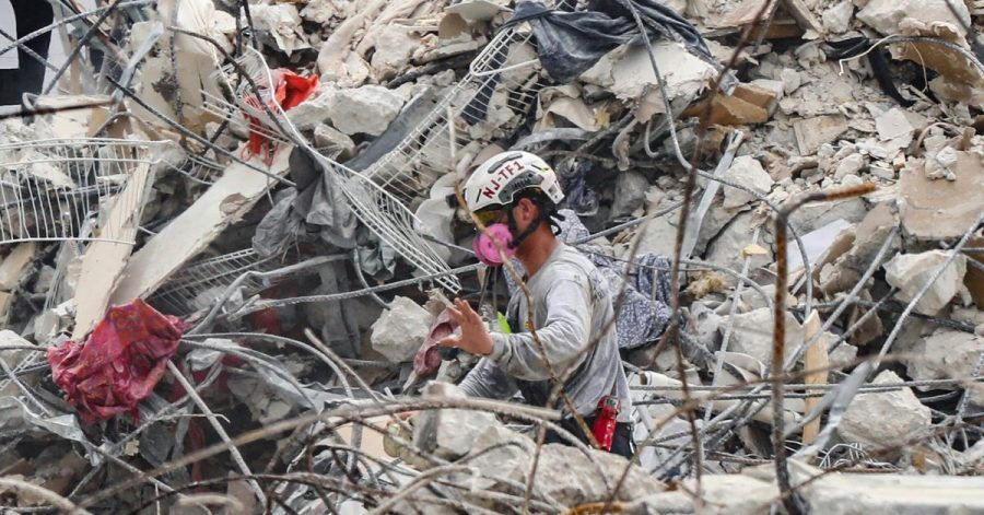 Rettungskräfte arbeiten sich durch dieTrümmern des teilweise eingestürzten Wohnkomplexes.