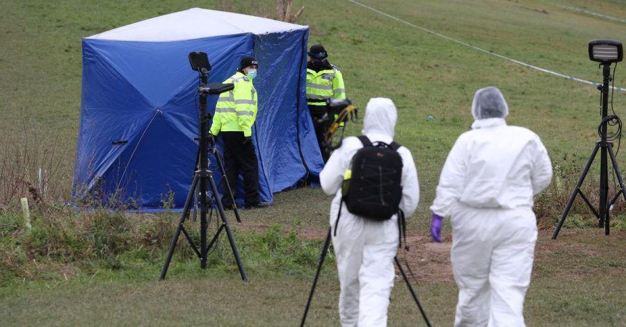 Zwei Gerichtsmediziner gehen zu einem Zelt am Tatort auf dem Bugs Bottom Feld. Fünf Jugendliche sollen hier im Januar einen 13-jährigen Jungen erstochen haben.