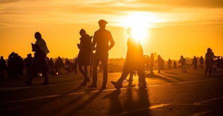 Menschen spazieren während des Sonnenuntergangs bei frühlingshaften Temperaturen auf dem Tempelhofer Feld in Berlin.