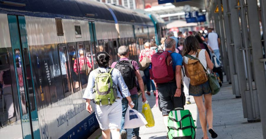 Voller Bahnsteig: Reisende gehen auf der Nordseeinsel im Bahnhof Westerland an einem Zug entlang.