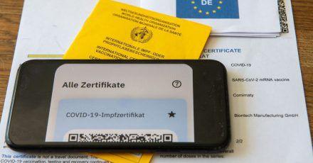 Ein Impfpass und ein Smartphone, auf dem die App CovPass läuft, liegen auf einem Impfzertifikat.