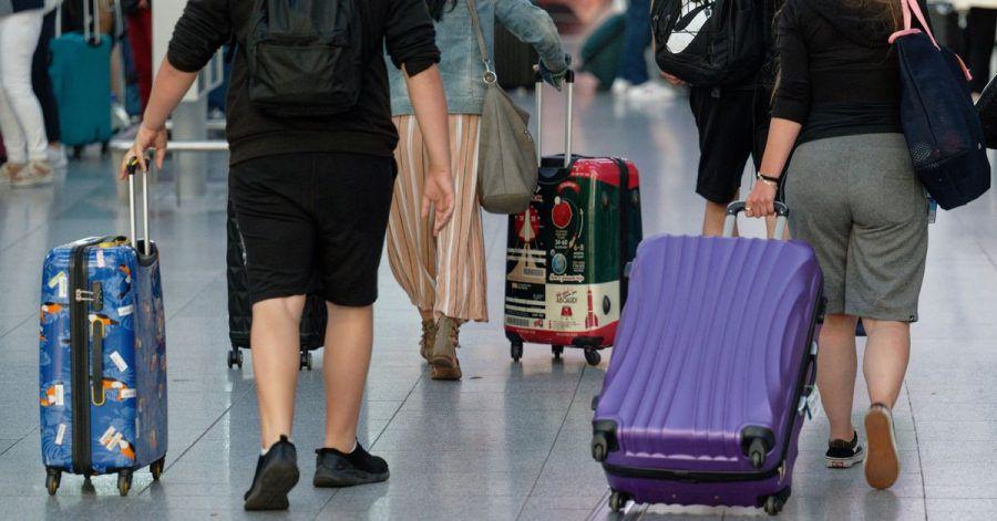 Reisende gehen im Flughafen Düsseldorf mit Koffern durch die Abflughalle.