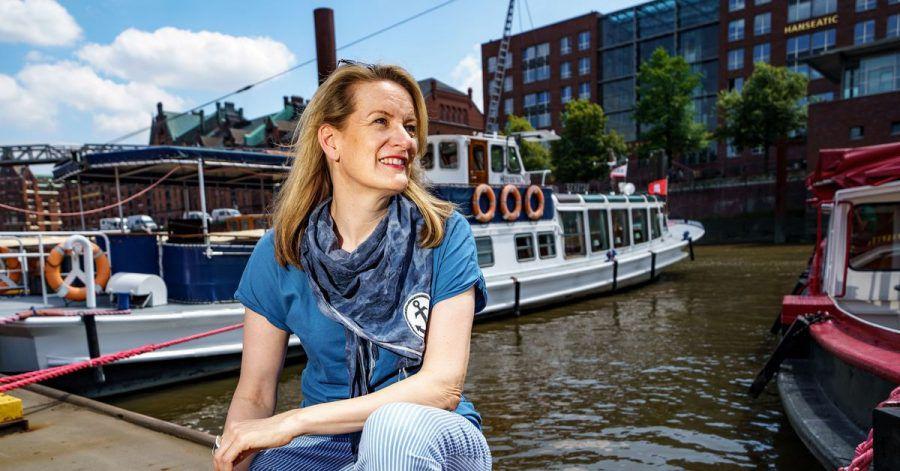 Tourguide Maike Brunk sitzt vor einer Tour durch den Hamburger Hafen vor einer Barkasse.