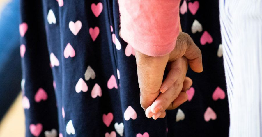 Eine Frau hält ein Mädchen an der Hand.