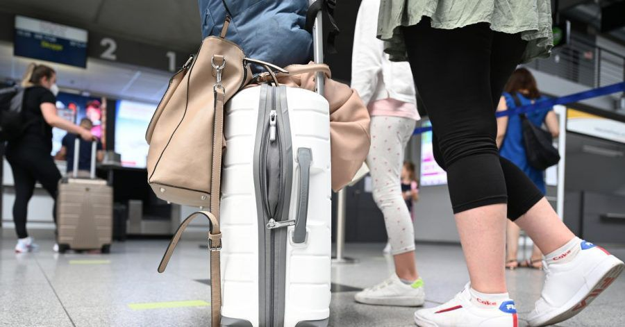 Reisende an einem Flughafen. Symbolbild