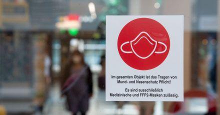 Ein Schild am Eingang zu einer Einkaufspassage weist auf das Tragen von Mund- und Nasenschutz hin.