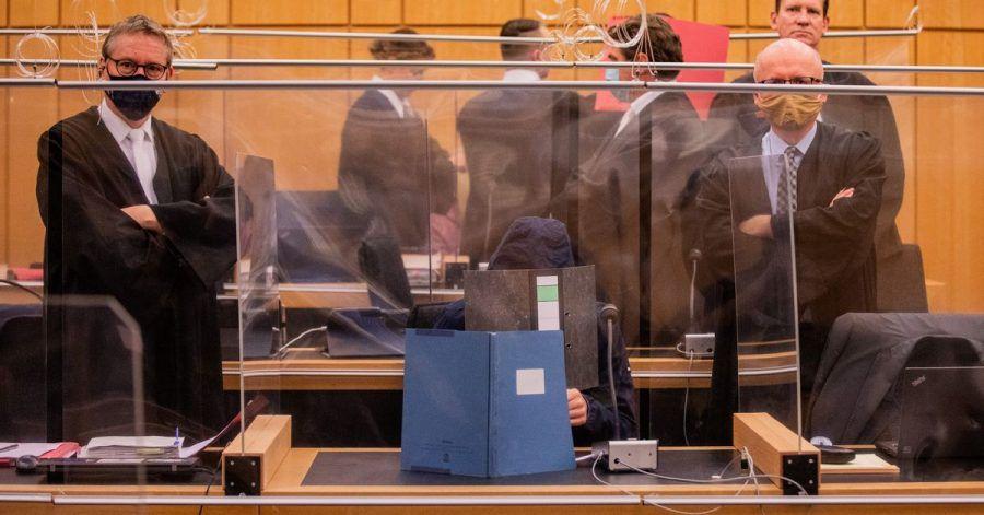Der damals 27-Jährige Hauptangeklagte (vorne), seine Mutter (ganz hinten links) und ein dritter Angeklagter (roter Hefter) sitzen in einem Gerichtssaal des Landgerichts.
