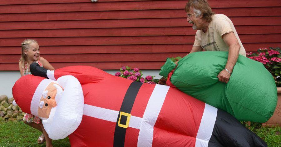 Lachend tragen Alicia und ihr Opa Dietmar Sawatzke den drei Meter großen aufgeblasenen Weihnachtsmann neben die mit Sommerblumen dekorierte Eingangstür.