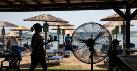 Eine Kellnerin serviert Erfrischungen in einer Strandbar im Dorf Lagonissi. Eine seit Anfang der Woche andauernde Hitzewelle in Griechenland erreicht ihren Höhepunkt.
