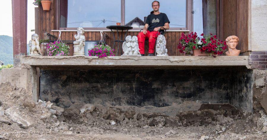 Daniel Schmitz sitzt auf dem Balkon seiner durch die Flut zerstörten Wohnung. Vom einst liebevoll gestalteten Garten ist nichts mehr übrig geblieben.
