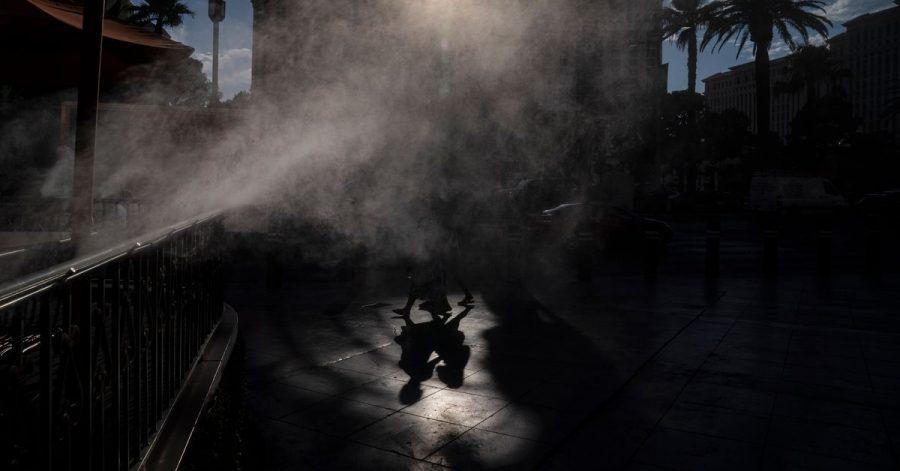 Menschen gehen in Las Vegas an Nebelmaschinen vorbei, die zur Abkühlung entlang der Casino-Meile eingesetzt werden.