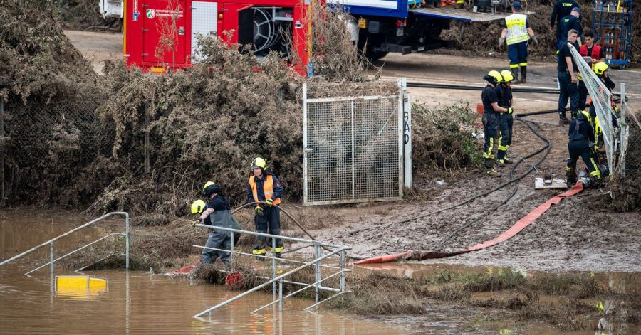 Helfer von Feuerwehr und Technischem Hilfswerk (THW) pumpen Wasser aus einem Regenrückhaltebecken ab, in dem sich noch Fahrzeuge befinden sollen.