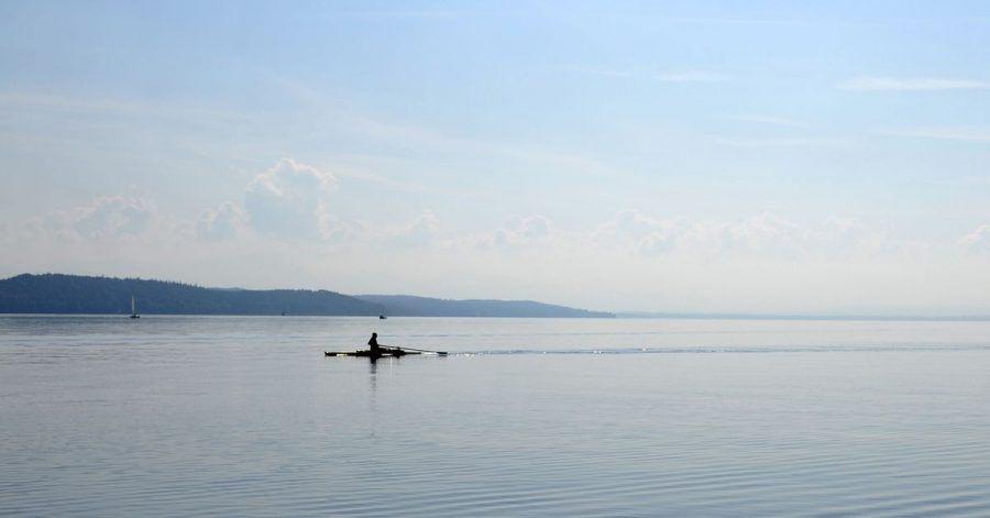 Ein Ruderer fährt bei Sonnenschein über den Starnberger See (Oberbayern).