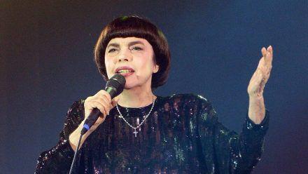 Schwarzes Kleid, Pagenfrisur, erhobene Hand: Mireille Mathieu steht noch auf der Bühne wie vor 50 Jahren. (tae/spot)