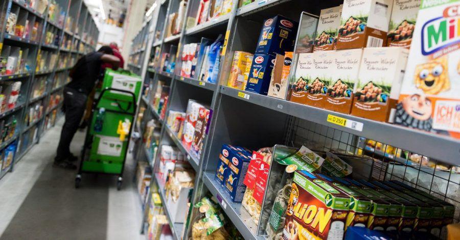 Ein Mitarbeiter eines Lebensmittellieferdienstes packt bestellte Waren ein. Der Online-Handel mit Lebensmitteln boomt.