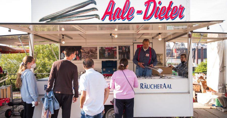 Besucher auf dem Hamburger Fischmarkt am Stand von Aale-Dieter.