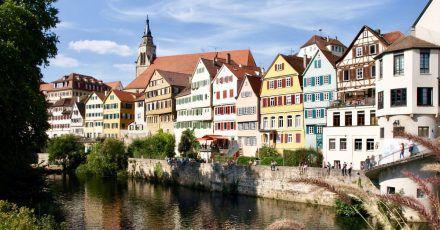 Der Bootsführer im Stocherkahn erklärt Touristen die Neckarfront inTübingen.