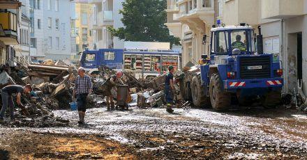 Mitarbeiter des Technischen Hilfswerks (THW) helfen bei Aufräumarbeiten nach der Unwetterkatastrophe in einer verschlammten Straße.