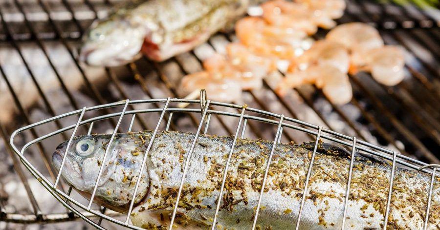 Die Forelle brutzelt in der Fischzange. So kommt sie nicht mit dem Rost in Berührung. Und damit die Garnelen nicht in die Glut fallen, stecken sie auf einem Holzspieß.