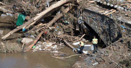 Polizisten suchen im Geröll an einer Ahrbrücke nach möglichen Opfern der Flutkatastrophe.