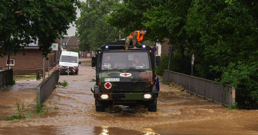 In Erftstadt bahnt sich ein Fahrzeug der Bundeswehr einen Weg durch eine überflutete Straße.