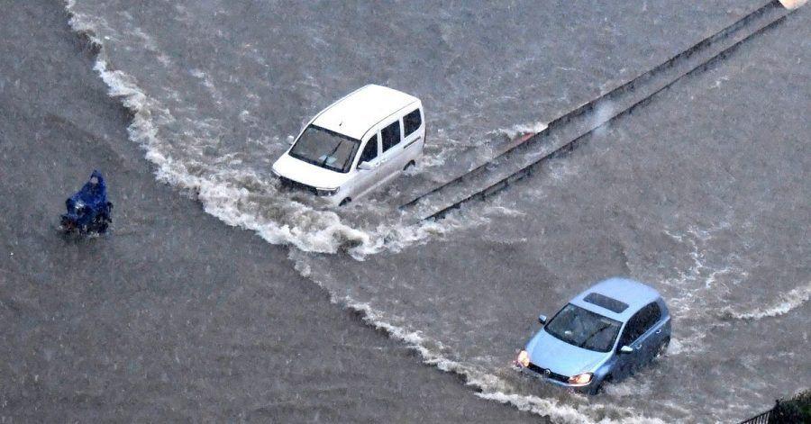 Fahrzeuge bahnen sich ihren Weg durch die Fluten in Zhengzhou in der zentralchinesischen Provinz Henan.