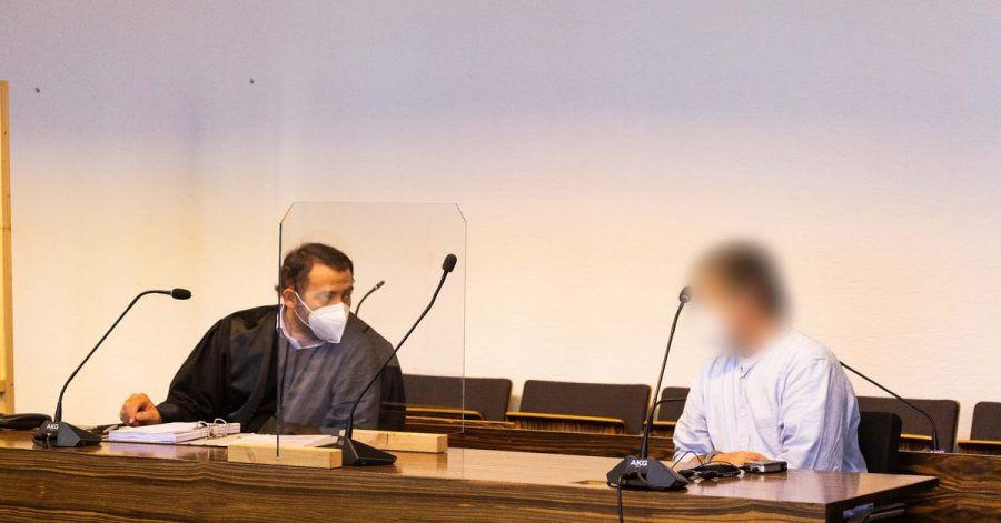 Ein Angeklagter sitzt im Gerichtssaal und hört seinem Anwalt zu.