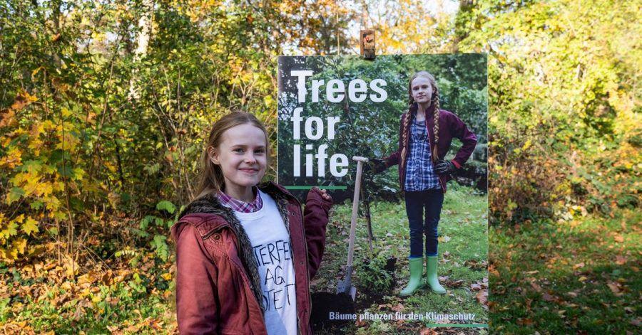 "Mirella Schulze (Tilda Jenkins) vor dem Kampagnenplakat zu ""Trees for Life""."