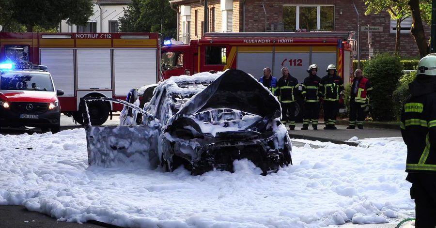 Vom Löschschaum bedeckt steht ein Auto nach einer Explosion auf der Straße im nordrhein-westfälischen Hürth.