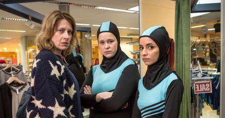 Wanda (Caroline Peters) kauft für ihre Tochter Nina (Chantal Zitzenbacher, M) und deren beste Freundin Maryam (Duygu Arslan) einen Burkini.