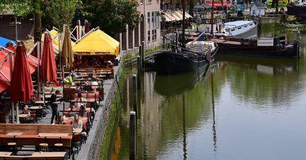 Nur wenige Gäste sitzen bei sonnigem Wetter in den Außenbereichen der Cafés und Restaurants am Historischen Hafen in Rotterdam (Archivbild).