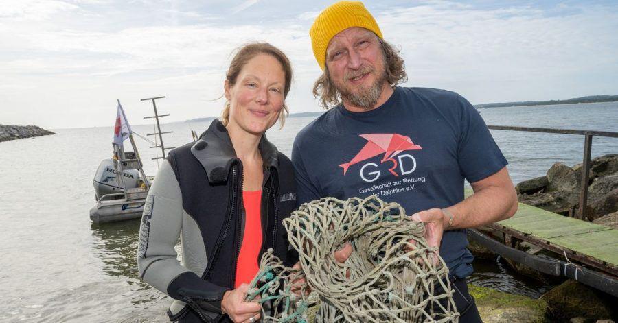 Das Schauspieler-Paar Tessa Mittelstaedt (47) und Matthias Komm (54) steht vor einem Tauchgang in die Ostsee vor der Insel Rügen an der Tauchbasis Mukran mit einem Netz in der Hand da.
