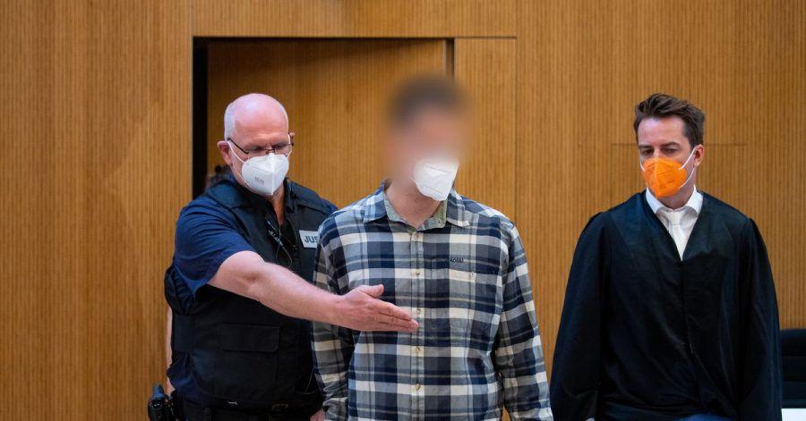 Einer von beiden wegen Mordes angeklagten Männer (m) wird in den Sitzungssaal geführt.