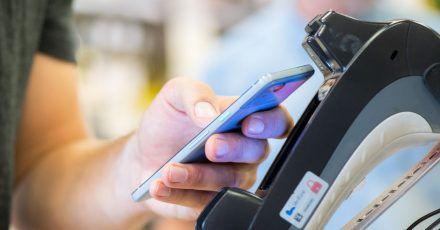 Ein Smartphone wird an ein Kassenterminal gehalten. Mit der entsprechenden App kann man so bezahlen.