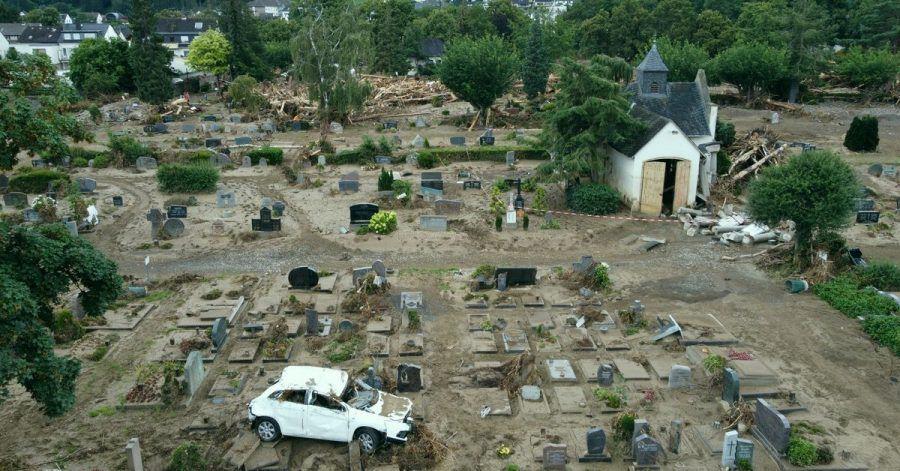 Ein Auto, das bei der Hochwasserkatastrophe auf den Friedhof geschwemmt worden ist, steht auf einem Grabfeld. Der Friedhof ist völlig zerstört.